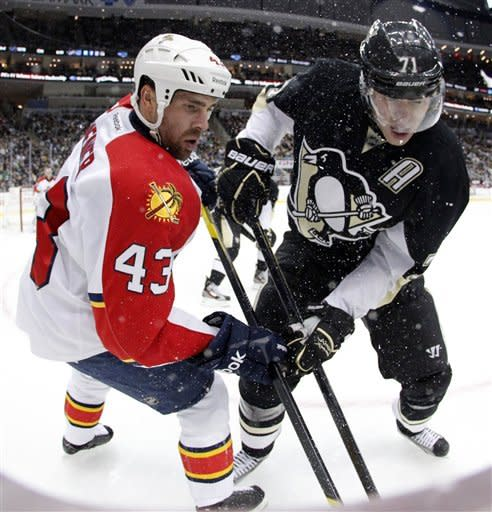 Pittsburgh Penguins' Evgeni Malkin (71) battles in the corner for the puck with Florida Panthers' Mike Weaver (43) in the second period of an NHL hockey game in Pittsburgh on Friday, March 9, 2012. (AP Photo/Gene J. Puskar)