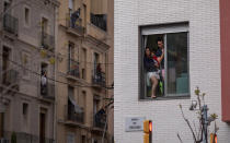 People stand in their balconies during a nationwide confinement to counter the coronavirus in Barcelona, Spain on March 29, 2020. (AP Photo/Emilio Morenatti)