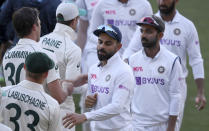 India's Virat Kohli, center, shakes hands with Australian players on the third day of their cricket test match at the Adelaide Oval in Adelaide, Australia, Saturday, Dec. 19, 2020. Australia won the match. (AP Photo/David Mariuz)