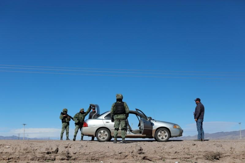 Soldiers check a vehicle at a check point in Janos, Chihuahua