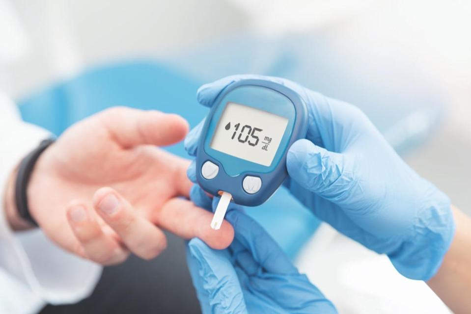 The doctor checks the blood sugar with a blood glucose meter.  Treatment concept of diabetes.