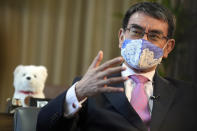 Taro Kono, Japan's minister in charge of a huge vaccination campaign, wearing a face mask speaks during an interview with The Associated Press at his office in Tokyo Wednesday, July 28, 2021. As Olympics host Tokyo saw another record number of coronavirus cases Wednesday, Kono told that the speed of the inoculation campaign, which is averaging about 10 million shots a week after a late start, is less urgent than getting shots to young people, who are blamed for spreading the virus. (AP Photo/Eugene Hoshiko)