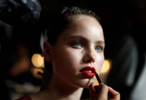 A model has her lipstick applied before a runway show in Australia. A new study has found potentially harmful chemicals called PFAS in makeup. (Jason Reed/Reuters - image credit)