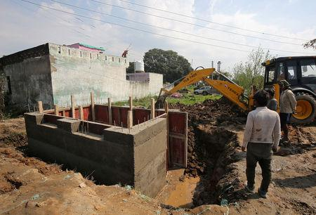 Workers construct a concrete bunker in a residential area near the border with Pakistan in Samba sector near Jammu February 26, 2019. REUTERS/Mukesh Gupta