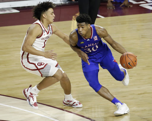 Kansas guard Ochai Agbaji (30) drives the ball against Oklahoma forward Jalen Hill (1) during the second half of an NCAA college basketball game in Norman, Okla., Saturday, Jan. 23, 2021. (AP Photo/Garett Fisbeck)