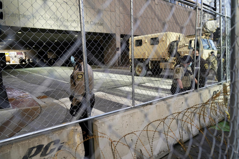 Sheriff deputies and National Guard troops maintain the fenced-off road leading to the Hennepin County Government Center, Monday, March 8, 2021, in Minneapolis where the trial for former Minneapolis police officer Derek Chauvin began with jury selection. Chauvin is charged with murder in the death of George Floyd during an arrest last May in Minneapolis. (AP Photo/Jim Mone)