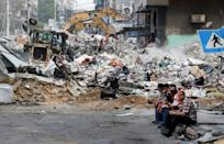 An excavator clears the rubble of a destroyed building in Gaza City's Rimal residential district on May 16
