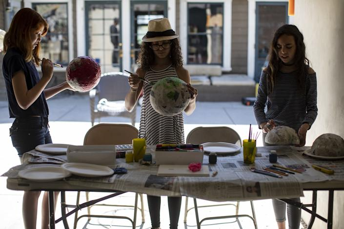 "Kat Bristow, left, Carmen Furbush and Penelope Roth work on papier-mache masks in art class inside the Roths' garage. <span class=""copyright"">(Gina Ferazzi / Los Angeles Times)</span>"