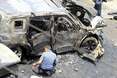A crime scene investigator investigates the site of a car bomb attack on the convoy of Egyptian public prosecutor Hisham Barakat near his house at Heliopolis district in Cairo, June 29, 2015. REUTERS/Mohamed Abd El Ghany