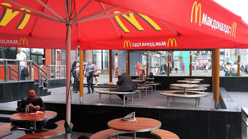 A man sits at a table outside a closed McDonald's restaurant, the first to be opened in the Soviet Union in 1990, in Moscow on August 21, 2014 (AFP Photo/Alexander Nemenov)