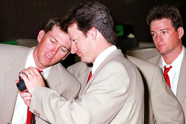Australian skipper Steve Waugh (2nd L) shows a picture on his digital camera to fast bowler Glenn McGrath (L) as Mark Waugh (R) looks on as the team arrives in Colombo 17 August 1999. The Australians have been assured security reserved for a visiting head of state in view of fears of attacks by rebel Tamils.  AFP PHOTO