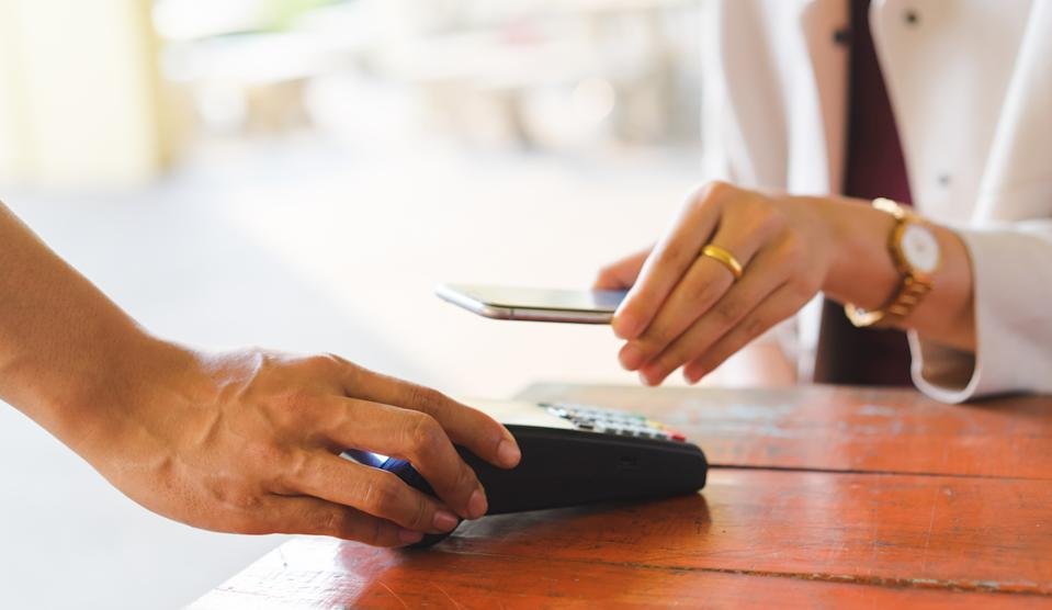 close up customer woman hand using smartphone for paying bill by using payment machine at table in the cafe , contactless payment concept