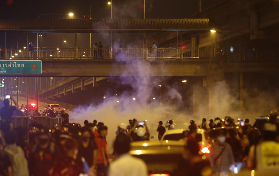 Riot policemen shoot tear gas on the road near to anti-government protesters, during a protest in Bangkok, Thailand, Sunday, Feb. 28, 2021. The anti-government protesters marched towards a military house where Prime Minister Prayuth Chan-ocha lives to call for monarchy reform and the military removal from the politics. (AP Photo)