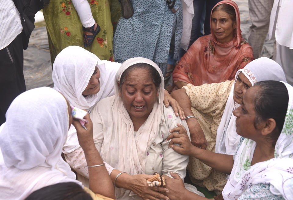 Relatives and neighbors of a farmer who was killed Sunday after being run over by a car owned by India's junior home minister mourn at Tikonia village in Lakhimpur Kheri, Uttar Pradesh state, India, Monday, Oct. 4, 2021. Indian police on Saturday, Oct. 9, arrested the son of a junior minister in Prime Minister Narendra Modi's government as a suspect days after nine people were killed in a deadly escalation of yearlong demonstrations by tens of thousands of farmers against contentious agriculture laws in northern India, a police officer said. (AP Photo)