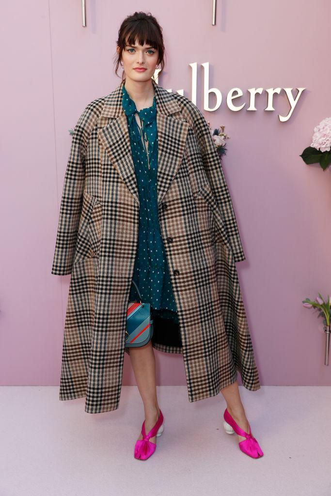 <p>Model Sam Rollinson rocked an oversized check coat to the show in true FROW style. <em>[Photo: Getty]</em> </p>