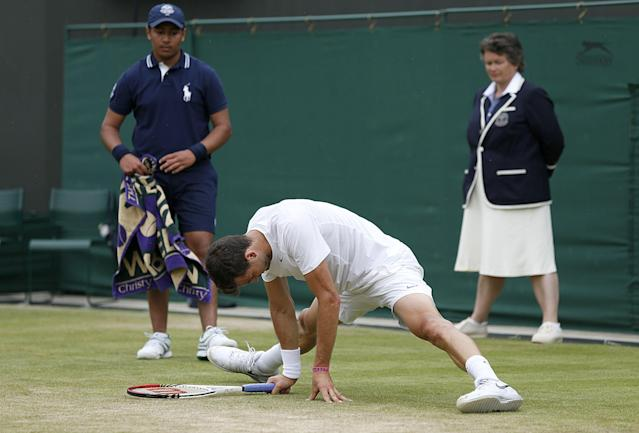 Bulgaria's Grigor Dimitrov slips on the grass against Slovenia's Grega Zemlja during day four of the Wimbledon Championships at The All England Lawn Tennis and Croquet Club, Wimbledon.