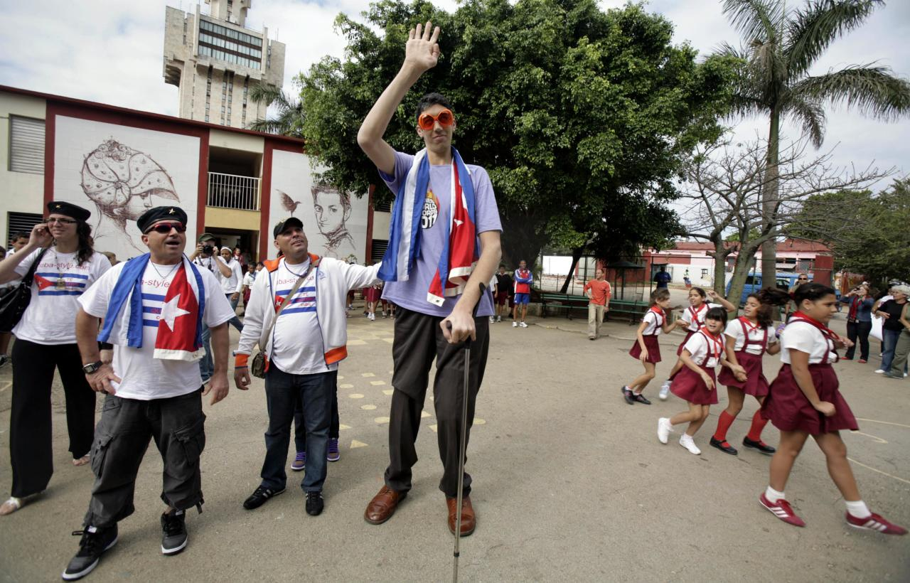 Sultan Kosen, center, 28, of Turkey, who according to the Guinness World Record Association is the world's tallest man, waves as he is accompanied by members of the newly-created Cuba Amore Foundation, during a visit to the Cesareo Fernandez school in Havana, Cuba, Monday, March 14, 2011. Kosen is part of a group of young people visiting Cuba with Cuba Amore Foundation, a solidarity organization.