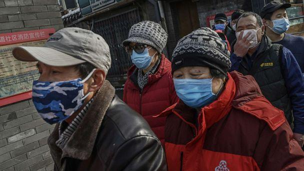 PHOTO: Local Chinese residents wear protective masks as they wait in line to get a ticket to receive free masks and cleaner outside a pharmacy in Beijing, Feb. 8, 2020. (Kevin Frayer/Getty Images)