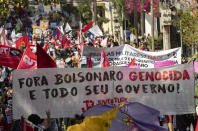 """Demonstrators march holding a banner with a message that reads in Portuguese; """"Get out genocidal Bolsonaro and all your government"""" during a protest against Brazilian President Jair Bolsonaro and his handling of the pandemic and economic policies protesters say harm the interests of the poor and working class, in Cuiaba, Brazil, Saturday, June 19, 2021. (AP Photo/Andre Penner)"""
