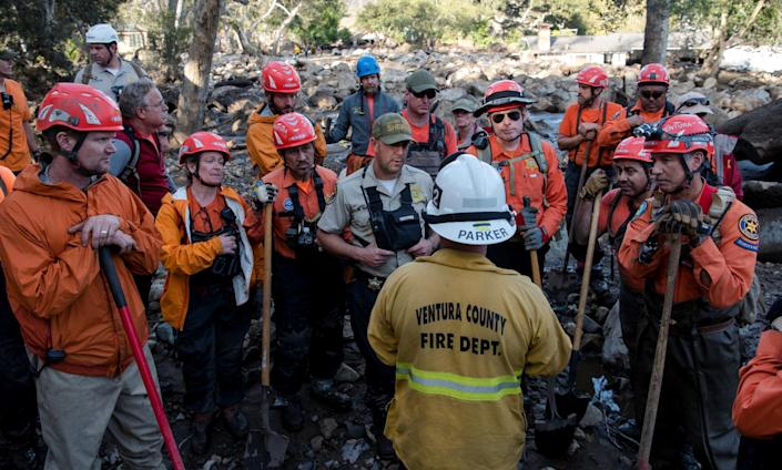 <p>Ventura Search & Rescue volunteers (in orange) listen to a briefing from a Ventura County firefighter on Glen Oaks Road in Montecito, Calif., Jan. 10, 2018. (Photo: Kenneth Song/Santa Barbara News-Press via Reuters) </p>