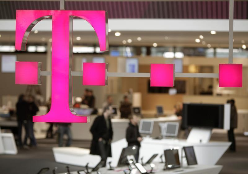 The sign of Deutsche Telekom AG is pictured at its stand for the upcoming CeBIT fair inside a hall in Hanover