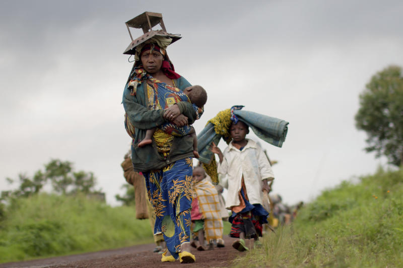 "A displaced Congolese family carry their belongings on the road between Rutshuru and Goma, after the village of Kibumba was occupied by an armed militia consisting of current or former members of the ""National Congress for the Defence of the People"", according to those fleeing, in Congo Tuesday, May 8, 2012. Mutinous soldiers formerly from the armed militia ""National Congress for the Defence of the People"" and linked to Congolese ex-general Bosco Ntaganda, who is wanted for alleged war crimes by the International Criminal Court, say they have formed a new rebel group called the ""March 23 Movement"", led by a colonel who was formerly the No. 2 in the army under Ntaganda. (AP Photo/Marc Hofer)"