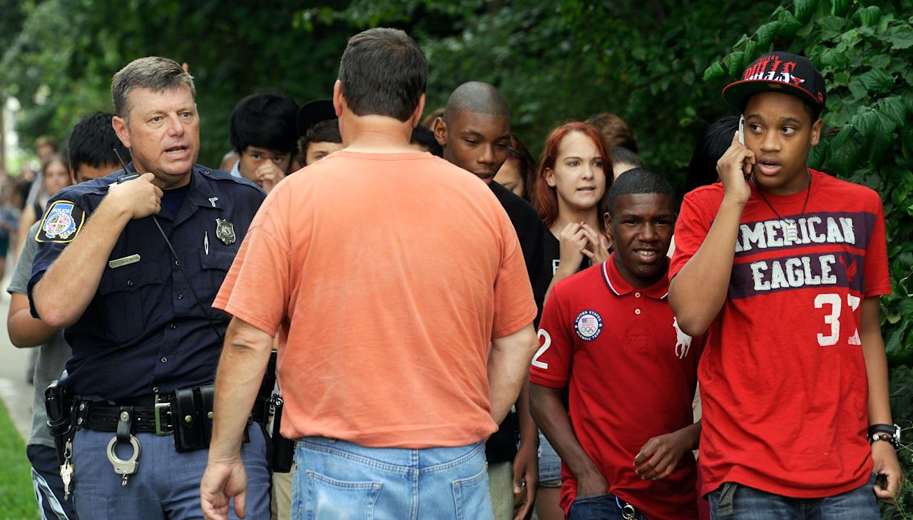 A Baltimore County police officer speaks to a parent as students are evacuated from Perry Hall High School after a student was shot and critically wounded on the first day of classes Monday, Aug. 27, 2012, in Perry Hall, Md. A suspect was taken into custody shortly after the shooting, according to police. No one else was reported injured. (AP Photo/Steve Ruark)