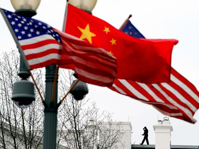 Aa Secret Service agent guards his post on the roof of the White House as a lamp post is adorned with Chinese and US national flags in Washington, DC: AFP via Getty Images