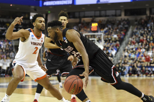 Gardner-Webb's DJ Laster (25) drives against Virginia's Braxton Key (2) during a first-round game in the NCAA men's college basketball tournament in Columbia, S.C., Friday, March 22, 2019. (AP Photo/Richard Shiro)