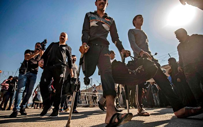 Men leave a Kurdish-run prison in northeast Syria in a general amnesty for low-level Islamic State prisoners - AFP