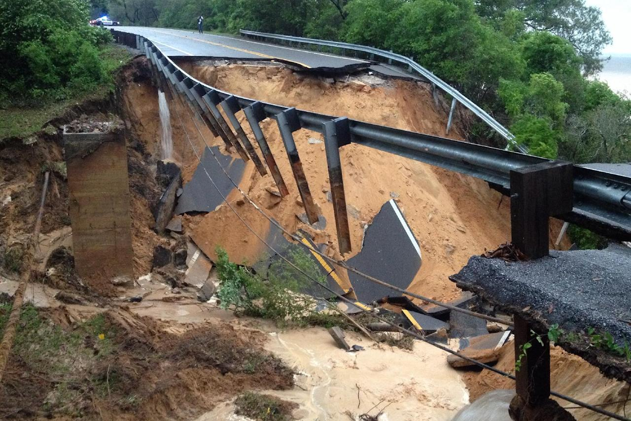 A portion of the Scenic Highway collapsed near Pensacola, Fla., Wednesday April 30, 2014. Heavy rains and flooding have left people stranded in houses and cars in the Florida Panhandle and along the Alabama coast. According to the National Weather Service, an estimated 15-20 inches of rain has fallen in Pensacola in the past 24 hours. (AP Photo/Pensacola News Journal, Katie E. King)