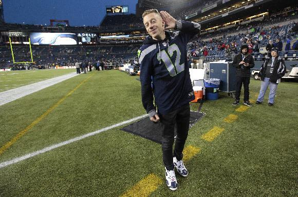 Seattle rap singer Macklemore responds to the crowd at CenturyLink Field prior to an NFL football game between the Seattle Seahawks and the San Francisco 49ers, Sunday, Dec. 23, 2012, in Seattle. (AP Photo/Elaine Thompson)