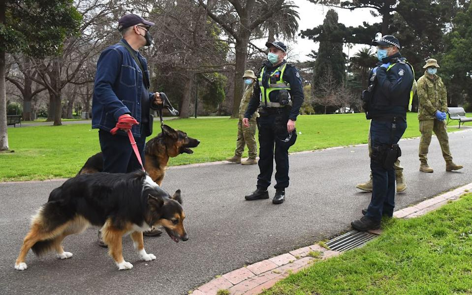 A man is seen wearing a mask while walking his dog as police officers and soldiers patrol Treasury Gardens in Melbourne. Source: Getty