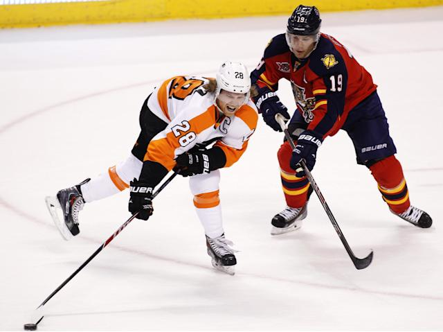 Philadelphia Flyers center Claude Giroux (28) carries the puck as Florida Panthers right wing Scottie Upshall (19) defends during the first period of an NHL hockey game in Sunrise, Fla., on Tuesday, April 8, 2014. (AP Photo/Terry Renna)