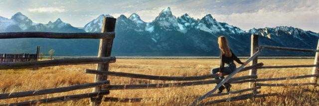Woman sitting on a fence looking at mountains.