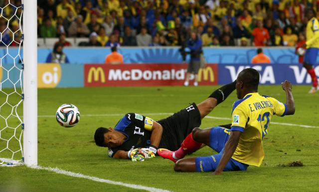 Ecuador's Enner Valencia scores past goalkeeper Noel Valladares of Honduras during their 2014 World Cup Group E soccer match at the Baixada arena in Curitiba June 20, 2014. REUTERS/Darren Staples (BRAZIL - Tags: TPX IMAGES OF THE DAY SOCCER SPORT WORLD CUP)