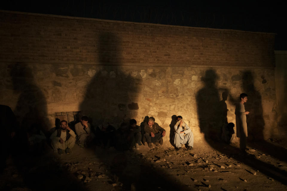 The shadow of Taliban fighters casts over drug users detained at a police station in Kabul, Afghanistan, Friday, Oct. 1, 2021. The Taliban are shifting from being warriors to an urban police force. (AP Photo/Felipe Dana)