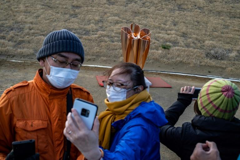 People take selfies in front of the Tokyo 2020 Olympic flame on display at Ishinomaki Minamihama Tsunami Recovery Memorial Park in Ishinomaki, Miyagi prefecture
