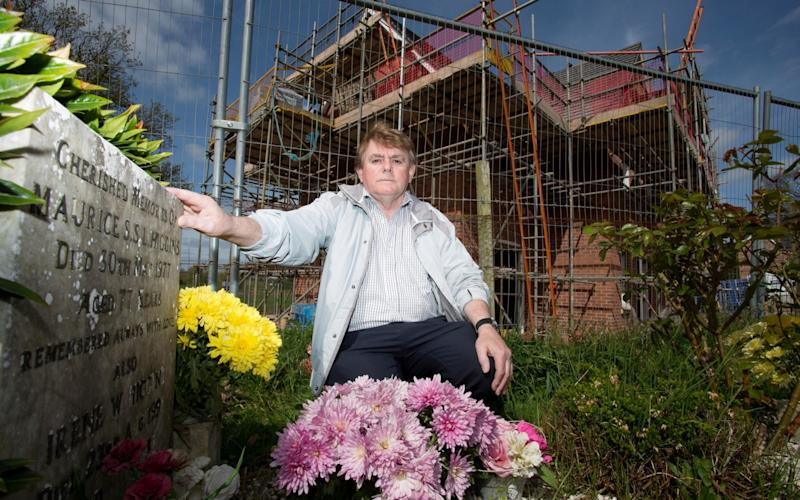 "A grieving son has been left ""disgusted"" after his parents' tranquil graves were ruined by a housing estate  - Credit: SWNS"