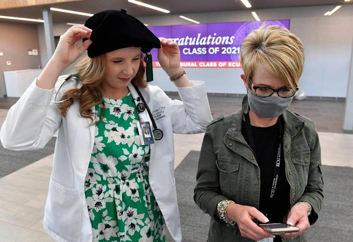 Cali Clark, left, is one of the first graduates of the new Kansas City University school of medicine in Joplin. She stopped by the student center on Friday afternoon to pick up her cap and gown from Haley Reardon, who searched for information on her phone about how to wear the fancy cap.