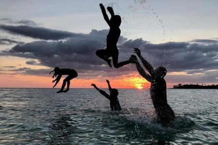 People have fun on a beach during sunset at Ko Kut island in Trat Province