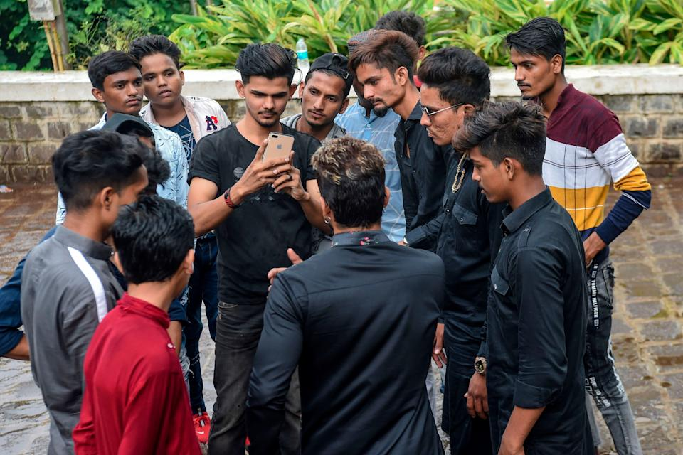 In this photo taken on November 10, 2019, youngsters gather around mentor Akhtar Shaikh (back to camera) before a video-recording session in Mumbai. Image used for representational purposes only in this article. (Photo: INDRANIL MUKHERJEE via Getty Images)