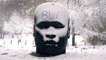 """The abbreviation """"BLM"""", for the Black Lives Matter movement, written on the forehead of the """"Eternal Presence"""" statue outside the National Center of Afro-American Artists, Friday, Oct. 30, 2020, in the Roxbury neighborhood of Boston. The Boston area was blanketed with a few inches of snow during the day. (AP Photo/Charles Krupa)"""