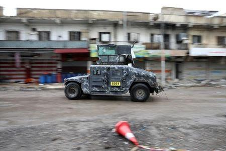 A vehicle of the Iraqi forces drives along a street controlled by the Iraqi Federal Police during combat with Islamic State in western Mosul