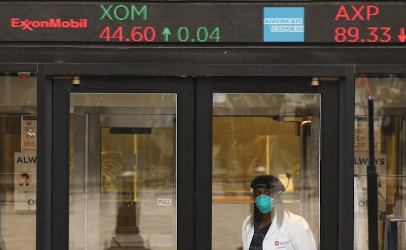 Woman in mask in front of share price board