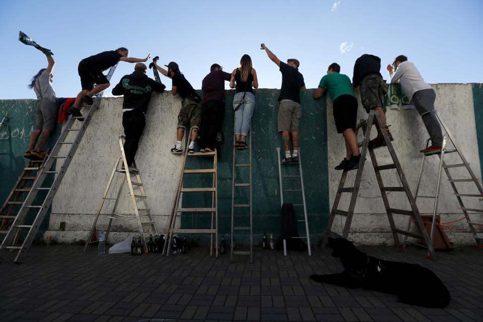Fans, standing on ladders from behind the fence, celebrate a goal as they watch a Czech first division match between Bohemians Prague and Zlin in Prague, Czech Republic, Sunday, Oct. 4, 2020. Amid restrictive measures that limit the number of soccer fans from attending the game, fans are looking for innovative ways to watch the match during the ongoing coronavirus pandemic. (AP Photo/Petr David Josek)