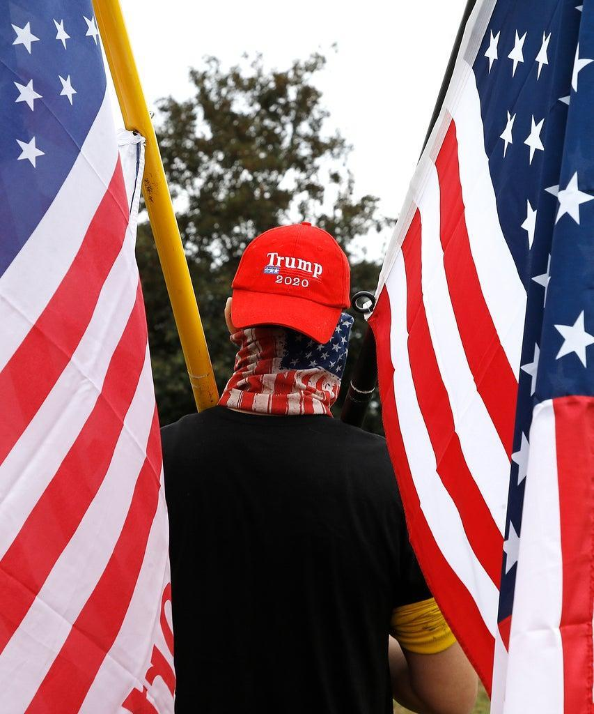 PORTLAND, UNITED STATES – 2020/09/26: A protester holds flags during the demonstration at Delta Park. Members of the far-right Proud Boys – some carrying firearms and wearing body armor – massed at a rally in Portland, Oregon, as counter rallies unfolded nearby and officials in the tense city braced for violence. (Photo by John Lamparski/SOPA Images/LightRocket via Getty Images)
