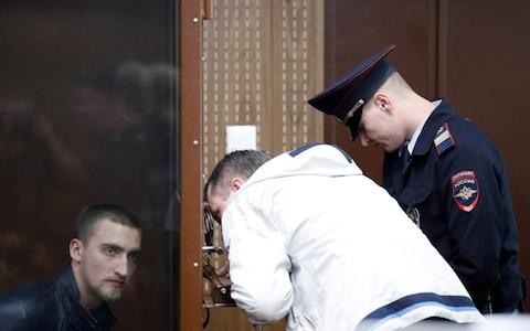 Pavel Ustinov listens to his lawyer from the defendant's cage on Monday - Credit: Evgenia Novozhenina/Reuters