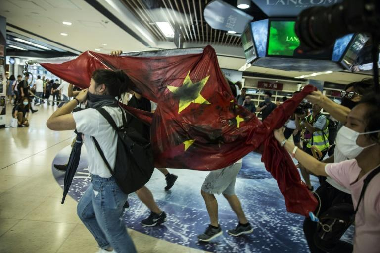 Masked activists paraded a Chinese flag through the mall that had been torn down from a nearby government building (AFP Photo/Isaac LAWRENCE)