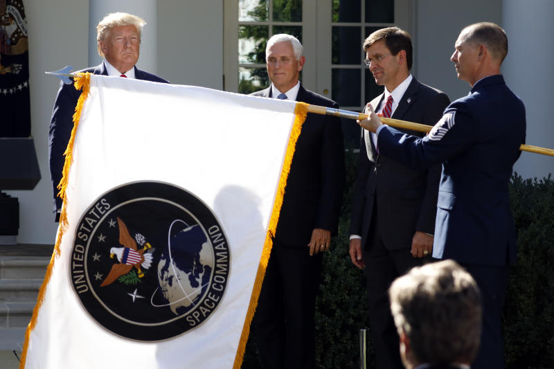 President Donald Trump watches with Vice President Mike Pence and Defense Secretary Mark Esper as the flag for U.S. space Command is unfurled as Trump announces the establishment of the U.S. Space Command in the Rose Garden of the White House in Washington, Thursday, Aug. 29, 2019. (AP Photo/Carolyn Kaster)